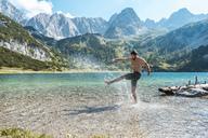 Austria, Tyrol, Young man at Lake Seebensee kicking water, having fun - DIGF04750
