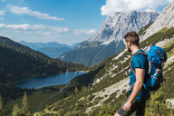 Austria, Tyrol, Young man hiking in the maountains at Lake Seebensee - DIGF04759