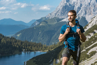 Austria, Tyrol, Young man hiking in the maountains at Lake Seebensee - DIGF04762