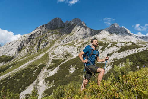 Austria, Tyrol, Young man hiking in the maountains at Lake Seebensee - DIGF04765