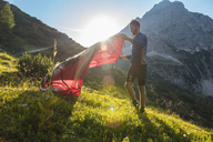 Austria, Tyrol, Hiker setting up his tent in the mountains - DIGF04777