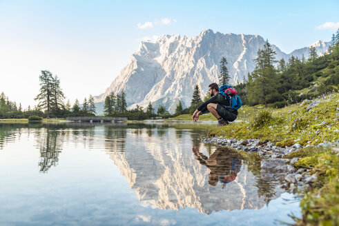 Austria, Tyrol, Hiker taking a break, crouching by the lake - DIGF04795