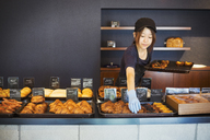 Woman working in a bakery, placing freshly baked croissants and cakes on large trays on a counter. - MINF07693