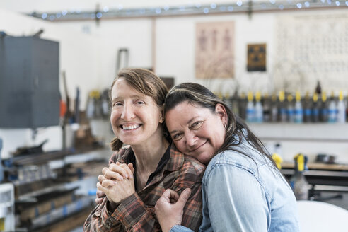 Two women standing in metal workshop, hugging and smiling at camera. - MINF07756