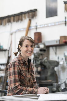 Blond woman wearing checked shirt standing in metal workshop, smiling at camera. - MINF07759