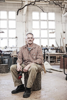 Caucasian man factory worker sitting on a stool in a woodworking factory. - MINF07942