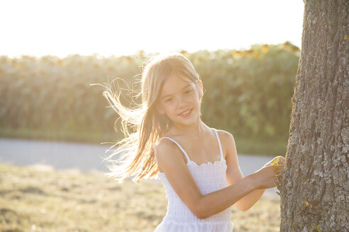 Girl standing on tree trunk at summer evening - LVF07389