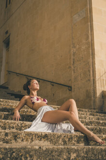 Teenage girl weraing long skirt and bikini top, posing on stairs - ACPF00198
