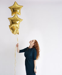 Young woman with three golden star-shaped balloons - ABIF00882