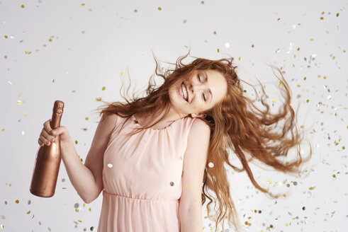 Portrait of happy young woman dancing with bottle of champagne - ABIF00888