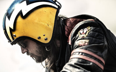 Profile of bearded man wearing yellow open face crash helmet and sunglasses. - MINF07950