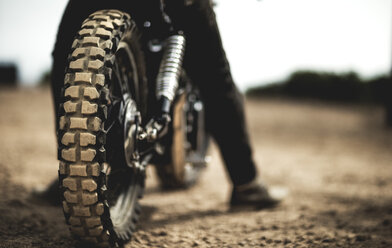Rear view of man sitting on cafe racer motorcycle on a dusty dirt road, close up of tire. - MINF07953