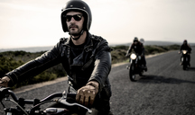 Man wearing open face crash helmet and sunglasses riding cafe racer motorcycle along rural road. - MINF07956