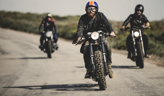 Three men wearing open face crash helmets and goggles riding cafe racer motorcycles along rural road. - MINF07959