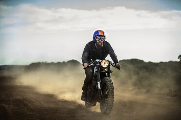 Man wearing open face crash helmet and goggles riding cafe racer motorcycle on a dusty dirt road. - MINF07962