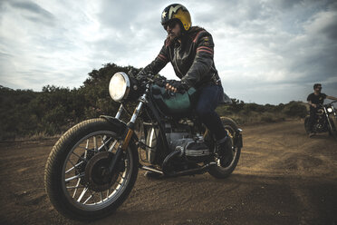 Man wearing open face crash helmet and sunglasses riding cafe racer motorcycle on a dusty dirt road. - MINF07965