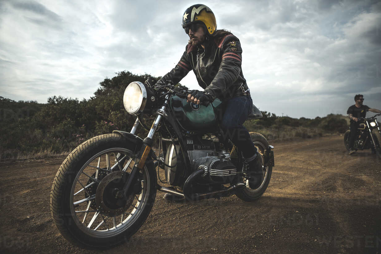 Man wearing open face crash helmet and sunglasses riding cafe racer motorcycle on a dusty dirt road. - MINF07965 - Mint Images/Westend61