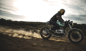 Side view of man wearing crash helmet riding cafe racer motorcycle on a dusty dirt road. - MINF07968