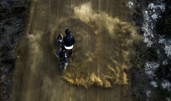High angle view of man driving cafe racer motorcycle in circles on a dusty dirt road. - MINF07971