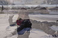 View through window at boy wearing furry hat standing the snow, throwing snowball. - MINF07986