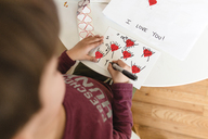 High angle view of boy standing indoors at a table, drawing red heart shapes onto piece of paper. - MINF08001