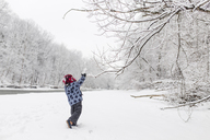 Boy wearing furry hat standing near a tree lined river in the snow, arm raised. - MINF08004