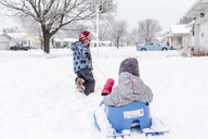 Boy wearing furry hat pulling young girl on a sledge cross snow-covered front lawn. - MINF08007