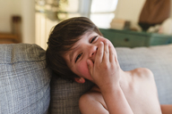 Boy with brown hair sitting indoors on a sofa, covering mouth with his hand, looking at camera. - MINF08019