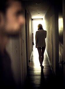 A woman walking down a corridor away from a man in the foreground. - MINF08079