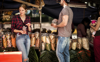 A couple shopping at a market stall piled with bags of snacks. - MINF08085