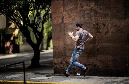 A man dancing on a city sidewalk. - MINF08091