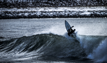 A young man surfing a wave, on a surfboard. - MINF08112