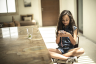 A girl sitting looking at a mobile phone screen. - MINF08124