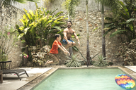 A man and boy in mid air, jumping into a swimming pool. - MINF08127