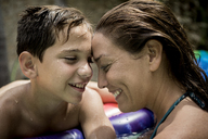 A woman and a boy cuddling in a swimming pool. - MINF08139