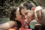 A woman and a boy cuddling in a swimming pool. - MINF08142