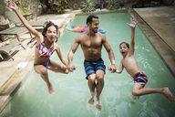 A man holding hands with two children jumping backwards into a swimming pool. - MINF08151