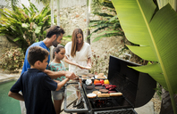 A family standing at a barbecue cooking food. - MINF08157