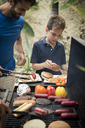 A man and boy standing at a barbecue cooking food. - MINF08160