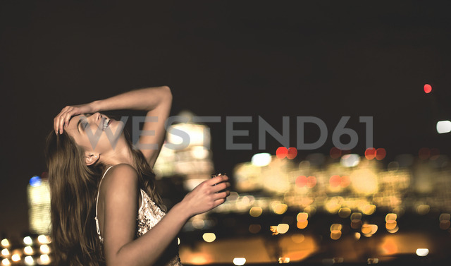 A young woman in a sequined party dress sitting on a rooftop at night with her head back and a drink in her hand. - MINF08178