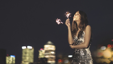 A young woman in a sequined dress dancing on a rooftop at night holding a party sparkler. - MINF08181