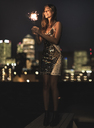 A young woman in a sequined dress dancing on a rooftop at night holding a party sparkler. - MINF08184