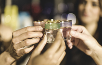 A group at a party holding shot glasses and celebrating. - MINF08187