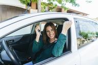 Woman inside of a car making triumph gesture - KIJF01992