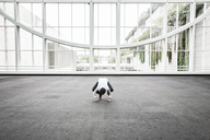 Businessman relaxing doing a yoga pose in a large open glass covered walkway. - MINF08206
