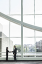 Businessman and woman meeting in a large glass covered walkway - MINF08212