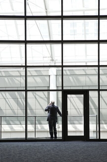 Businessman in a large lobby area - MINF08218