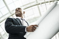 A black businessman holding plans for a new office space in a large glass covered walkway. - MINF08221