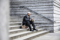 Black businessman taking a break for lunch sitting on a stairway step. - MINF08224