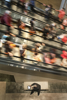 Businessman on a notebook computer near an escalator full of people. - MINF08233